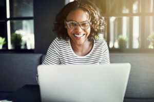 Female using laptop while smiling