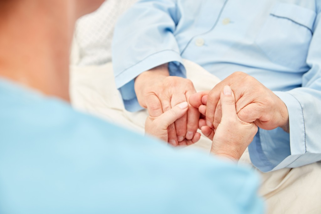 nurse holding the patient's hand
