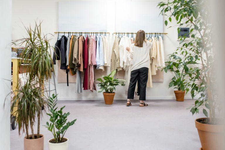 woman choosing clothes - rack of shirt