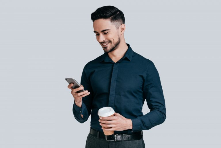 man holding coffee and using mobile phone