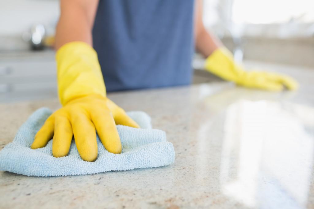 woman sanitizing a countertop